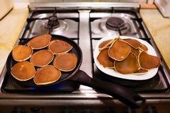 Het maken van pannekoeken in een zwarte pan royalty-vrije stock afbeelding