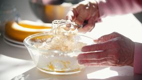 Het maken van pannekoeken Mengt de handen van oude vrouw de ingrediënten stock videobeelden