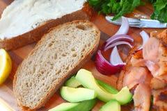 Het maken van sandwich met gerookte zalm en avocado stock foto