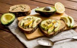 Het maken van sandwiches met hoogste mening van de avocado de gezonde natuurvoeding stock afbeeldingen