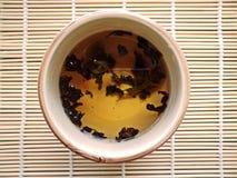 Het maken van thee in een glastheepot op geweven bamboeachtergrond Stock Foto