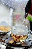 Het maken van thee tegen venster met regenachtige dagmening Stock Afbeeldingen