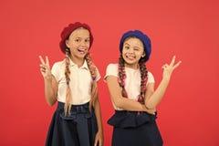 Het maken van vredestekens Franse stijlmeisjes Kleine jonge geitjes die modieuze Franse baretten dragen Leuke meisjes die hetzelf stock afbeeldingen