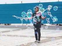 Het Maleise meisje maakt grote bellen in een openbare openluchtplaats van Kuching stock foto's