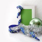 Het malplaatje van de groetkaart van wit kader en groene kaart met blauw lint, groene bal en zilveren klatergoud wordt gemaakt da Stock Afbeelding