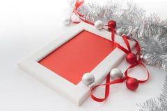 Het malplaatje van de groetkaart van wit kader en rode kaart met rood lint wordt gemaakt, zilveren en rode ballen en zilveren kla Royalty-vrije Stock Foto's