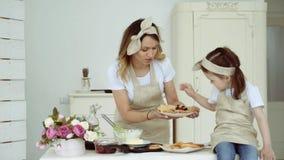 Het mamma behandelt een kleine dochter aan pannekoeken stock videobeelden