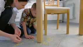 Het mamma berispt haar zoon voor verspreid voedsel op de keukenvloer en maakt hem schoonmaken De jongen maakt cornflakes van scho stock video