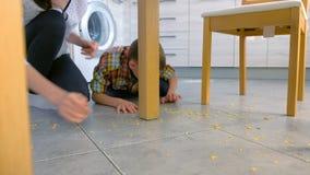 Het mamma berispt haar zoon voor verspreid voedsel op de keukenvloer en maakt hem schoonmaken Maak cornflakes van de vloer schoon stock footage