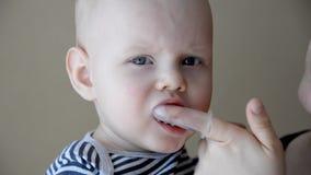 Het mamma borstelt melktanden met een borstel die op haar vinger past stock footage