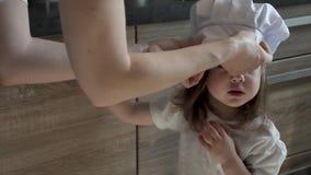 Het mamma draagt een kokende kap op haar weinig dochter stock videobeelden