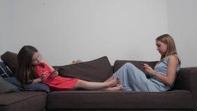 Het mamma en de baby zitten in de telefoons stock video