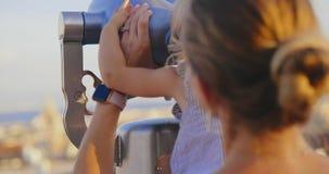Het mamma en de dochter bekijken door verrekijkers stad stock footage