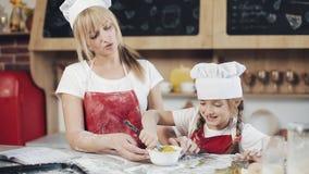Het mamma en de dochter in dezelfde kleren hebben pret voorbereidend een deeg op een comfortabele keuken Zij die eieren in kom me stock footage
