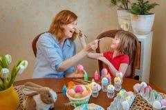 Het mamma en de dochter hebben pret het schilderen eieren voor Pasen stock foto's