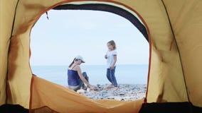 Het mamma en de dochter in het kamperen bouwen een open haard van stenen op overzees strand stock footage