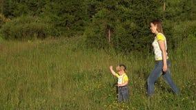 Het mamma en de dochter lopen in het park Familie in openlucht op een zonnige dag Kinderen met moeder in openlucht in de zomer A stock video