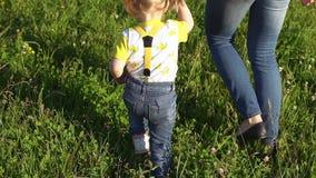 Het mamma en de dochter lopen in het park Familie in openlucht op een zonnige dag Kinderen met moeder in openlucht in de zomer A stock videobeelden