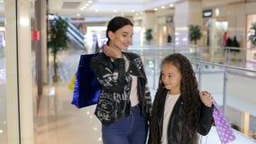 Het mamma en de dochter lopen in de wandelgalerij met zakken in hun handen stock footage