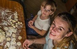 Het mamma en de dochter maken bloem uit bloem om bollen te koken Stock Afbeeldingen