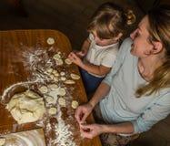 Het mamma en de dochter maken bloem uit bloem om bollen te koken Stock Foto's