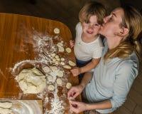 Het mamma en de dochter maken bloem uit bloem om bollen te koken Stock Fotografie