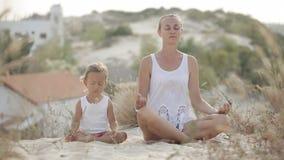 Het mamma en de dochter mediteren stock footage
