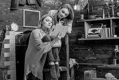 Het mamma en de dochter met geconcentreerd kijken samen lezend, het concept van het huisonderwijs Mooie blonde langs geamuseerde  royalty-vrije stock fotografie