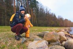 Het mamma en de dochter werpen stenen in het water op vakantie Gelukkige mensen Royalty-vrije Stock Afbeelding