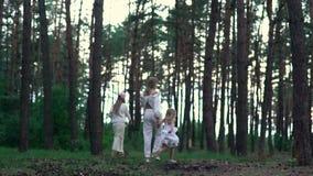 Het mamma en de dochter in witte kleding lopen rond het gebied dichtbij het bos stock videobeelden