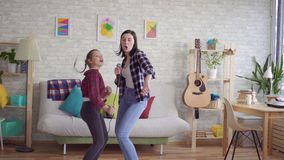 Het mamma en de dochter zingen thuis emotioneel karaoke