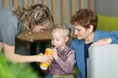Het mamma en de grootmoeder een drank aan geven haar de kleindochter van weinig dochter royalty-vrije stock afbeeldingen