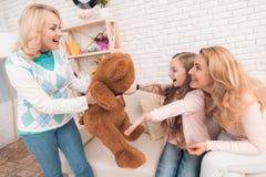 Het mamma en de grootmoeder geven een klein meisje een groot stuk speelgoed draagt royalty-vrije stock afbeeldingen