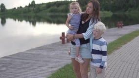 Het mamma en de kinderen lopen langs de dijk in de golfclub stock videobeelden