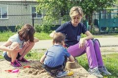Het mamma en de kinderen spelen op het hof stock foto's
