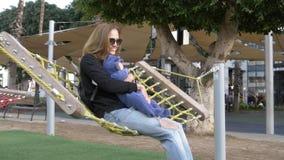 Het mamma en de kleine grappige baby hebben pret het shakeing in hangmat stock footage