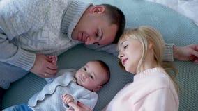 Het mamma en de papa liggen op het bed in het midden stock video
