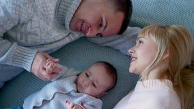 Het mamma en de papa liggen op het bed in het midden stock footage