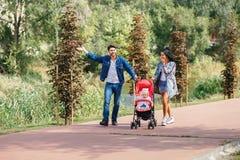 Het mamma en de papa lopen in het park met hun dochter in een wandelwagen, een mooie zonnige dag, een mooie familie stock foto