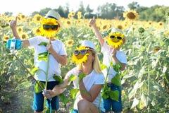 Het mamma en de zonen lopen rond het gebied met zonnebloemen Een gelukkige dag royalty-vrije stock afbeelding