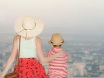 Het mamma en de zoon en bekijken de stad van een hoogte Achtermening, die tijd gelijk maken Stock Fotografie