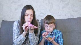 Het mamma en de zoon blazen grote bellen van op slimes Spel met slijm stock footage