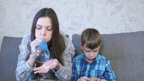 Het mamma en de zoon blazen grote bellen van op slimes Spel met slijm stock videobeelden