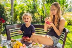 Het mamma en de zoon hebben ontbijt op het terras royalty-vrije stock afbeelding