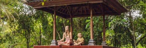 Het mamma en de zoon mediteren het praktizeren yoga in de traditionele BANNER van balinessegazebo, lang formaat royalty-vrije stock foto