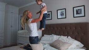 Het mamma en de zoon spelen op het bed in een heldere slaapkamer, een jongen van twee jaar lach en glimlachen stock footage