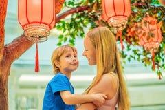 Het mamma en de zoon vieren Chinees Nieuwjaar bekijken Chinese rode lantaarns royalty-vrije stock afbeeldingen