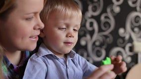 Het mamma en de zoon vormen thuis plasticine stock video