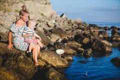 Het mamma en de zoon zitten op de stenen op het strand en het glimlachen Royalty-vrije Stock Foto