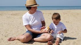 Het mamma en de zoon zitten op het strand op een zonnige de zomerdag Familievakantie en picknick in aard Het kind eet en stock video